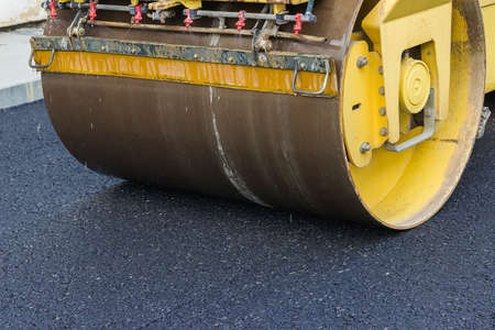compacting: Close of road roller compacting asphalt. Compactor roller during street paving works. Selective focus and shallow dof.