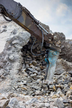 jack tar: Excavator arm with with hydraulic breaker or jackhammer crashing reinforced concrete. Stock Photo