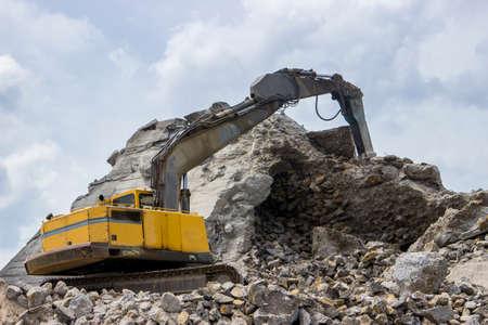 jack tar: Excavator with hydraulic breaker or jackhammer crashing reinforced concrete.