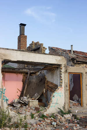 desolation: Ruined house after demolition. Destroyed interior and collapsed exterior wall.