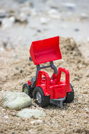 Wheel loader toy on the beach. Selective focus and shallow dof.