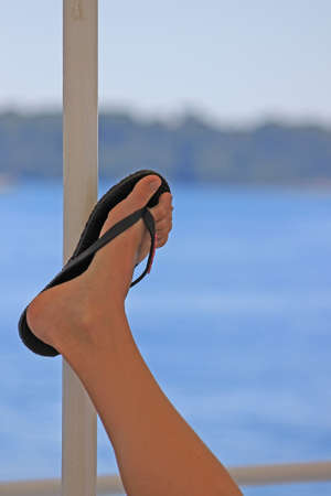 flops: Woman leg with beach flip flops sandals in the boat. Travel concept.