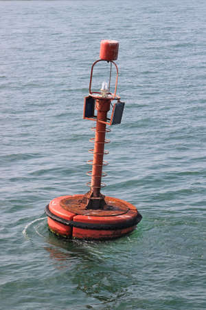 safe and sound: Red navigation buoy with solar panels floating on the sea.
