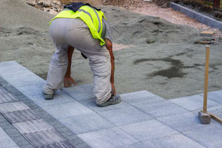 paver: Sidewalk paver installation in progress. Sidewalk revitalization. Focus on worker.