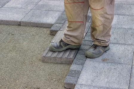 blinder: Installing tactile paving, path for blind handicap on the sidewalk. Sidewalk pavement for vision impaired people. Shallow dof.