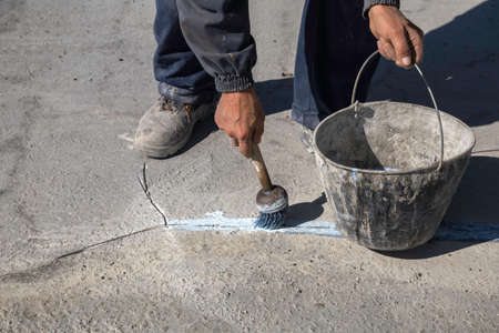 patching: Worker apply layer of bonding adhesive to the repair area using a paint brush. Bonding adhesive helps sealing a crack in concrete material. Stock Photo