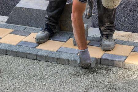 revitalization: Sidewalk paver installation in progress. Sidewalk revitalization. Focus on hands. Stock Photo