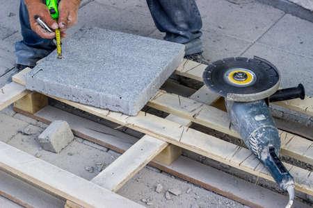 cutoff blade: Cut bricks with a angle grinder, sidewalk paver installation in progress, install pavers. Stock Photo