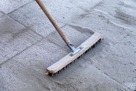 brooming: Install polymeric sand by brooming it into the paver joints during construction works. Some motion blur present.