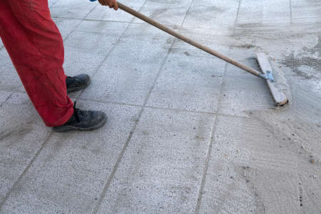 brooming: Install polymeric sand by brooming it into the paver joints during construction works. Stock Photo