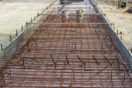 concreting: Metal bars and framework reinforcement for concrete pouring at construction site, during concreting supports for the tram tracks. Shallow dof. Stock Photo