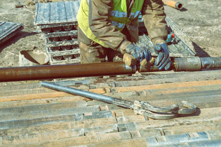 Drilling worker tightens drill pipe on core drilling platform. Made with shallow dof and vintage style.