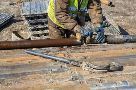 depletion: Drilling worker tightens drill pipe on core drilling platform. Made with shallow dof.