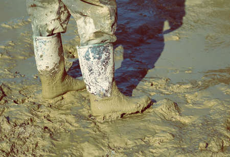 muddy clothes: Muddy work boots, human leg with dirty rubber boots. Made with shallow dof and vintage style.
