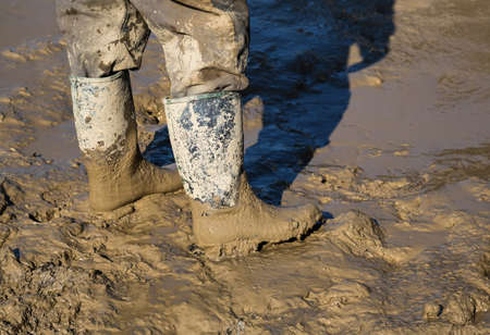 specific clothing: Muddy work boots, human leg with dirty rubber boots. Made with shallow dof.