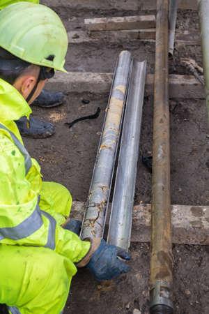 Techniker hält eine Kernprobe, gerade gebohrten Gesteins- und Sedimentproben, die später analysiert wird. Hergestellt mit selektiven Fokus und und flachen DOF. Standard-Bild - 48200546