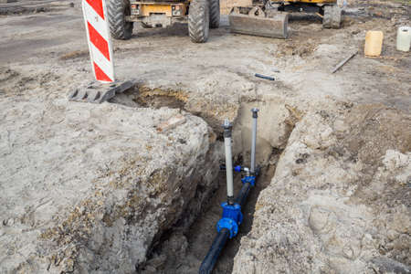 trench: Construction of new water line. Laying new water pipeline and water valve in a trench. Stock Photo