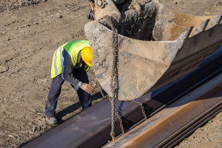 Bauarbeiter Befestigung Hebeketten auf Stahlprofil für Baggerschaufel Hebe. Hergestellt mit selektiven Fokus. Standard-Bild - 51011903