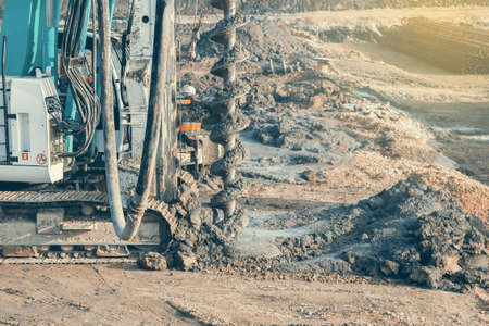 Drilling tractor installs concrete piles in the ground at construction site. Selective focus  and vintage style.