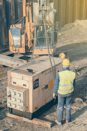 Workers installing electric generator at construction site. Standby generator, combination of an engine and an alternator for generating electricity. Selective focus and vintage style.