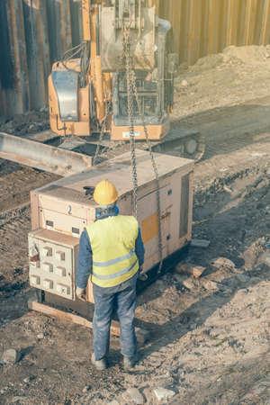 Arbeiter der Installation von elektrischen Generator auf der Baustelle. Standby-Generator, Kombination aus einem Motor und einem Generator zur Stromerzeugung. Selektiver Fokus und Vintage-Stil. Standard-Bild - 51012026
