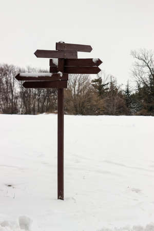 blank spaces: Wooden direction sign covered with snow and blank spaces for text