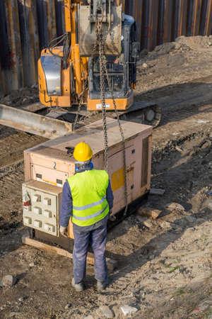 Arbeiter Installation elektrischer Generator auf der Baustelle. Notstromaggregat, Kombination aus einem Motor und einem Generator zur Stromerzeugung. Selektiver Fokus. Standard-Bild - 51012128