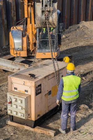 alternateur: Les travailleurs de l'installation génératrice électrique au chantier de construction. groupe électrogène de secours, la combinaison d'un moteur et un alternateur pour produire de l'électricité. mise au point sélective.