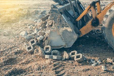 cargador frontal: cargador frontal con cangilón gran carga de residuos de hormigón para el reciclado en obras de construcción. enfoque selectivo y el estilo de la vendimia.