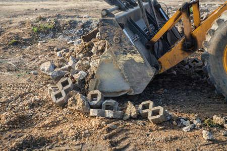 cargador frontal: cargador frontal con cangilón gran carga de residuos de hormigón para el reciclado en obras de construcción. enfoque selectivo