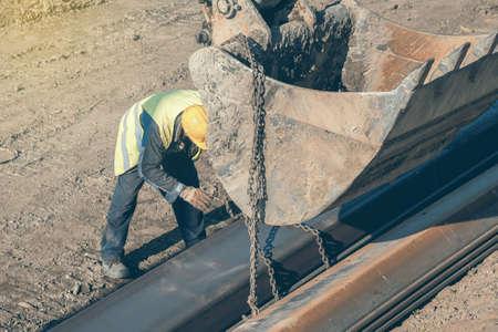 Bauarbeiter Befestigung Hebeketten auf Stahlprofil für Baggerschaufel Hebe. Hergestellt mit selektiven Fokus und Vintage-Stil. Standard-Bild - 51012370