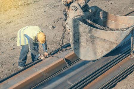 Bauarbeiter Befestigung Hebeketten auf Stahlprofil für Baggerschaufel Hebe. Hergestellt mit selektiven Fokus und Vintage-Stil. Standard-Bild - 51012374
