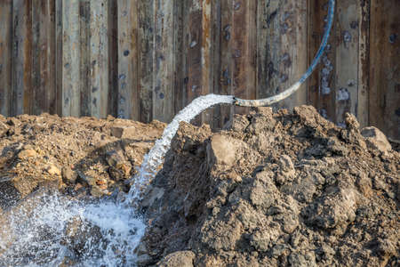 groundwater: Detail of dewatering construction site. Pumping water out of the construction site. Construction dewatering and groundwater pumping. Made with selective focus. Stock Photo