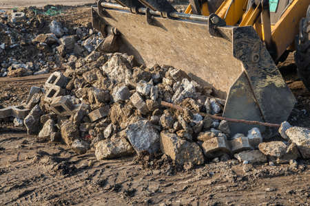 cargador frontal: cargador frontal con cangilón gran carga de residuos de hormigón para el reciclado en obras de construcción. enfoque selectivo.
