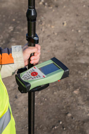 GNSS receiver with field controller on smart pole for surveying. GPS surveying instrument. Selective focus.