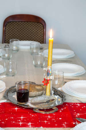 Holiday table with candle, cup of wine and sweet wheat in a bowl. Selective focus.