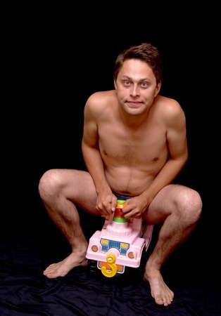 nackter mann: Der nackte Mann sitzt an einem Ruder der Kinder-Maschine