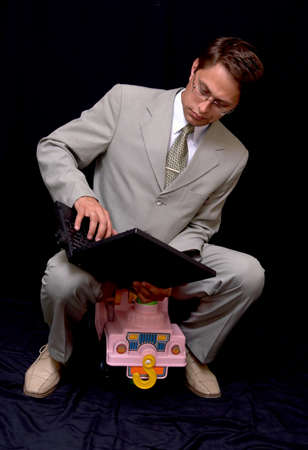 puerile: The businessman works on the computer sitting on the childrens automobile