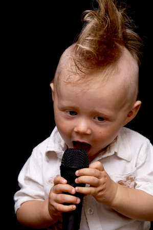 topknot: Portrait of the boy, singing in a microphone, with a ridiculous hairdress Stock Photo