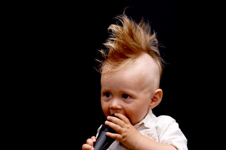 Portrait of the boy, singing in a microphone, with a ridiculous hairdress Stock Photo