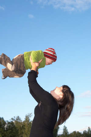 The mother lifts the son to the sky photo