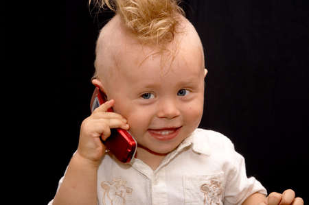 topknot: Portrait of the boy speaking on a cellular telephone Stock Photo