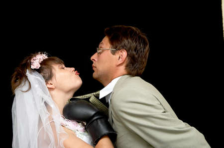 constraint: The bride kisses the groom on a black background