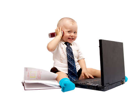 The small boy sits with the computer on a white background photo