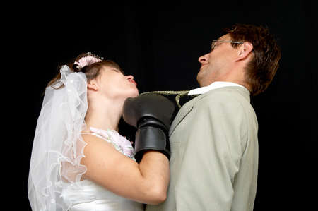 The aggressive bride and groom on a black background photo