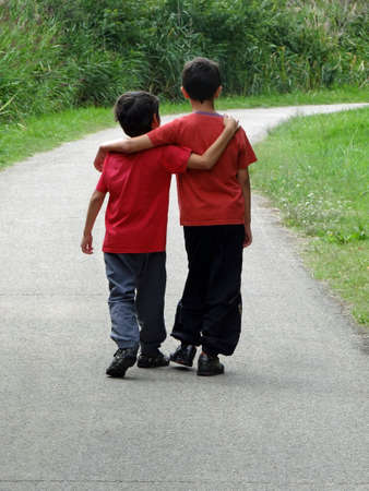 walking path: two children walking along a path                              Stock Photo