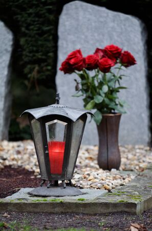 grave lantern with burning candle on a grave in front of a bouquet of red roses in a blurred background