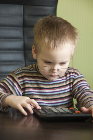 tally: a little boy with glasses counts on the calculator Stock Photo