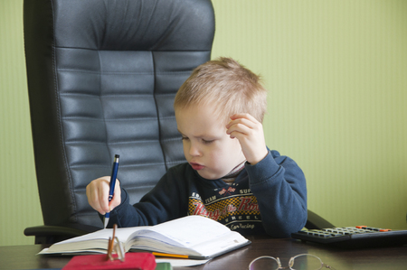 actuary: boy sitting on a leather chair at the table and looking in the diary entries