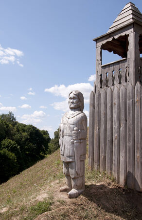 wooden statue of a knight near wooden fence